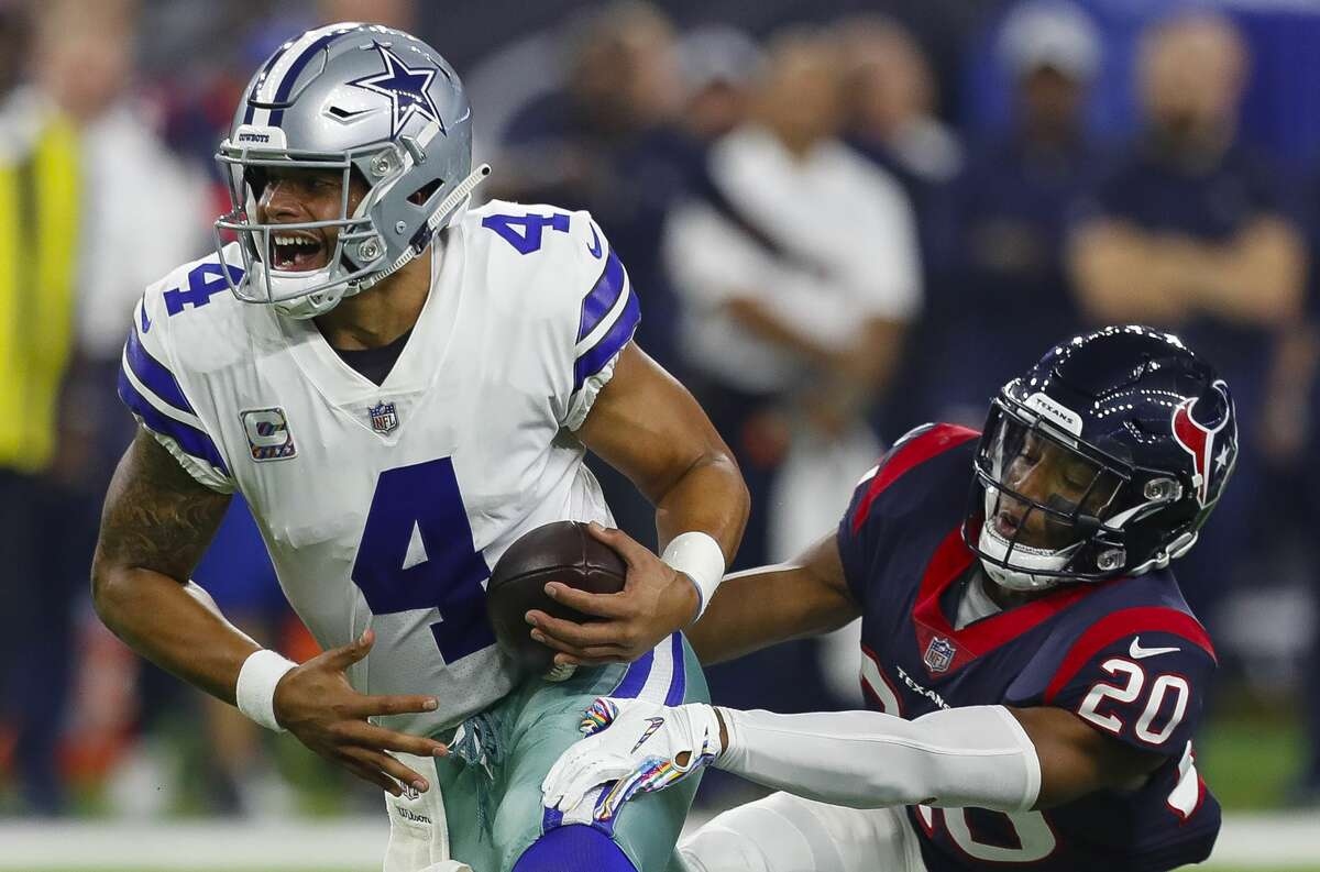Houston Texans defensive back Justin Reid (20) tries to drag down Dallas Cowboys quarterback Dak Prescott (4) during the second quarter of an NFL football game at NRG Stadium on Sunday, Oct. 7, 2018, in Houston.