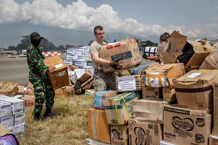 PALU, INDONESIA - OCTOBER 09: US Air Force military carry aid supplies at the Mutiara Sis Al Jufri on October 9, 2018 in Palu, Indonesia. The death toll from last week's earthquake and tsunami reached nearly 2,000 but officials have warned another 5,000 people are still missing and feared dead. Some schools reopened in the Indonesian city of Palu as children returned on Monday to tidy up their classrooms but the number of people in Sulawesi requiring aid has risen to 200,000 and some affected towns remain inaccessible with the infrastructure badly damaged. The deadly tsunami triggered by a magnitude 7.5 earthquake slammed into Indonesia's coastline on the island of Sulawesi last month which destroyed or damaged over 70,000 homes and tensions remain high with survivors trying to secure basics like food and water. (Photo by Ulet Ifansasti/Getty Images) Photo: Ulet Ifansasti / Getty Images / 2018 Getty Images