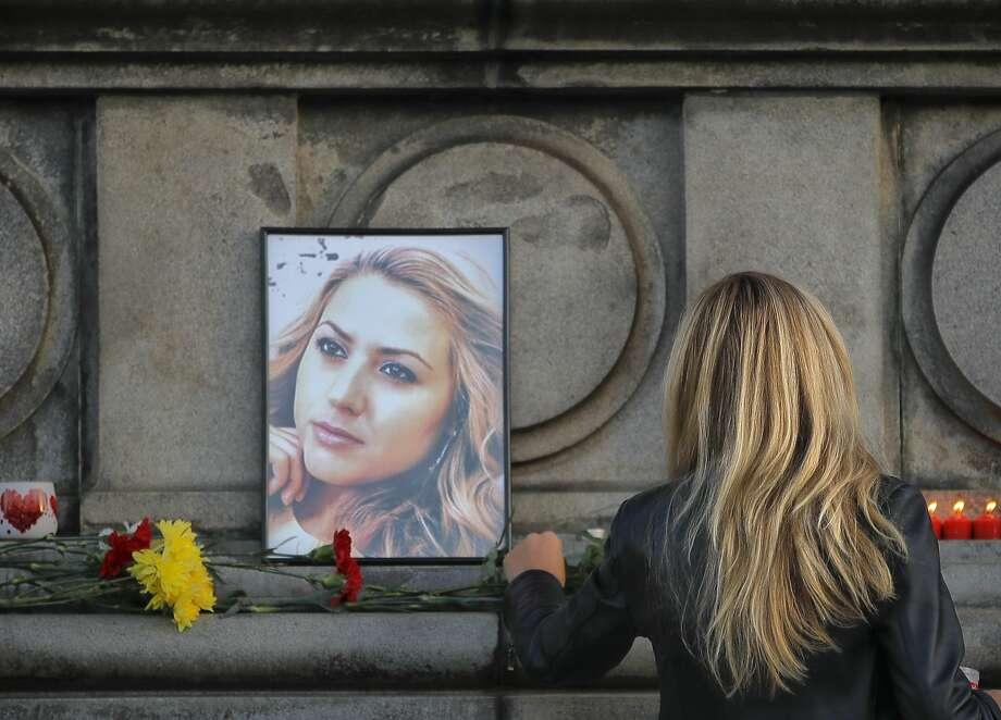 A woman places flowers next to a portrait of slain TV reporter Viktoria Marinova in Ruse, Bulgaria. Photo: Vadim Ghirda / Associated Press