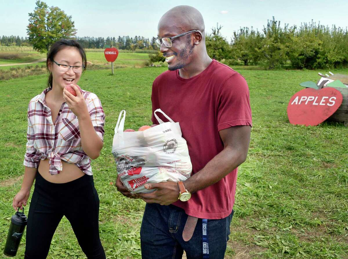 Emily Fitzgerald, left, of Springvale, Maine, samples an apple as she and Clifton Amponsah of Colonie pick their own at Indian Ladder Farms Tuesday Oct. 9, 2018 in Altamont, NY. (John Carl D'Annibale/Times Union)