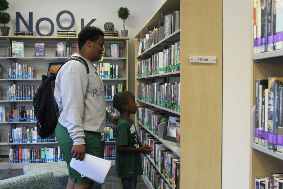 Senior Tre Caraway and kindergartener Bryce Tyree peruse library books during The John Cooper School's Senior-Kingergarten Adoption Day Oct. 5, 2018. Photo: Jane Stueckemann/The Villager / Jane Stueckemann/The Villager
