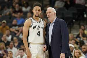 San Antonio Spurs head coach Gregg Popovich, right, talks to Spurs guard Derrick White during the first half of an NBA preseason basketball game against the Miami Heat, Sunday, Sept. 30, 2018, in San Antonio. San Antonio won 104-100. (AP Photo/Darren Abate)