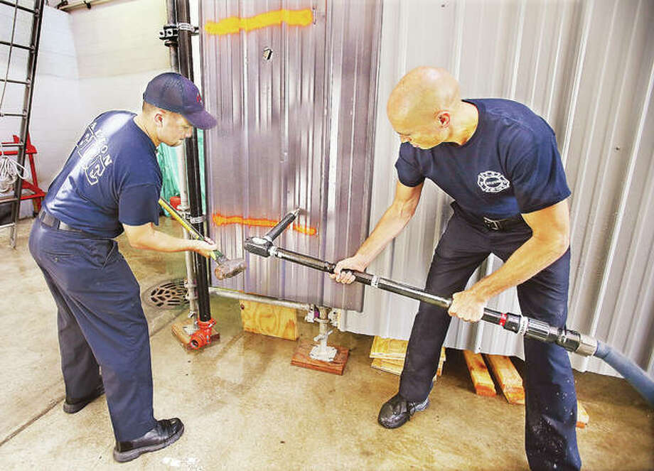 "In this photo from August, Alton Fire Department Capt. Rick Newman, right, holds the department's new ""piercing nozzle"" as firefighter Jacob Iman, left, prepares to hammer it through a piece of sheet metal during an operational demonstration. The nozzle was paid for with a 2017 grant from Illinois American Water as part of the company's ongoing support of local fire departments. Alton, among other local departments, was chosen by the company to receive additional grant funding this year. Photo: John Badman 