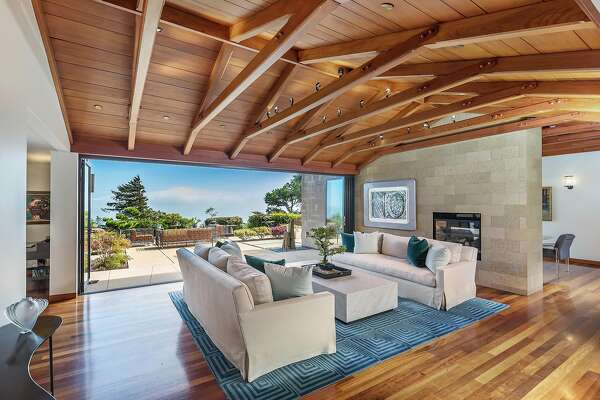 The great room at 93 Cloud View Road in Sausalito features a vaulted ceiling and stone wall with a gas fireplace.