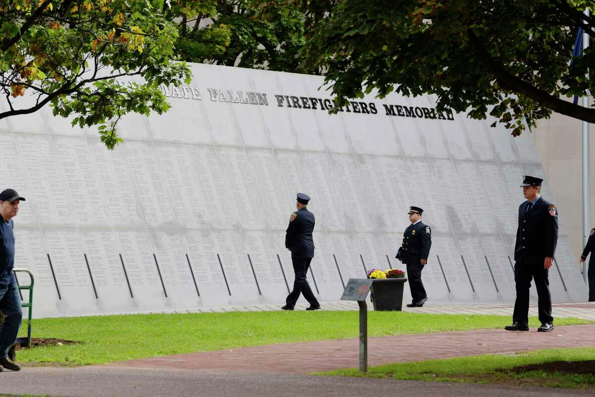 Firefighters visit the New York State Fallen Firefighters Memorial on the Empire State Plaza before the start of a memorial service on Tuesday, Oct. 9, 2018, in Albany, N.Y. This year the names of 28 firefighters who gave their lives in the line of duty were added to the wall. (Paul Buckowski/Times Union)