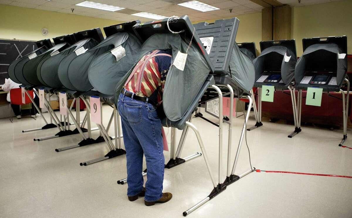 An election clerk prepares voting booths at the Metropolitan Multi-Services Center in Houston.