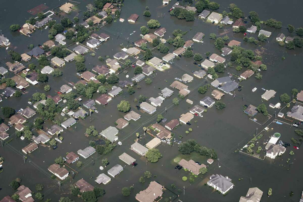 Floodwater surrounds homes in Beaumont, Texas, about 70 miles east-northeast of Houston, Aug. 31, 2017. With most roads in and out of the area under water, and the Neches River still rising, federal officials are trying to get enough bottled water into Beaumont to prevent a health crisis. (Alyssa Schukar/The New York Times)