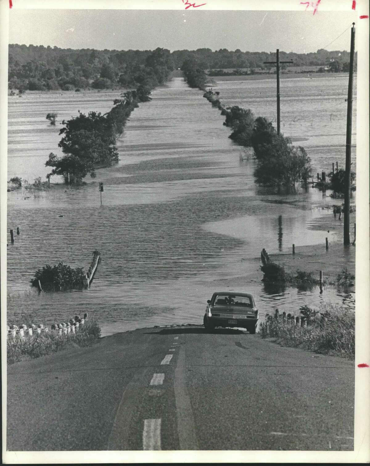 """Water from recent heavy rains has left at least two roads in the Addick's Reservoir area flooded and impassible. Pictured is a stretch of Eldridge Road north of the Katy Freeway, an abandoned car now stands clear of the receding water. Patterson Road just south of Bear Creek park also remained under water. Floods - Houston, Texas. The car obviously """"drowned out"""" and the water receded leaving it high and dry. Car sits where flooding begins - Eldridge Road in Houston."""