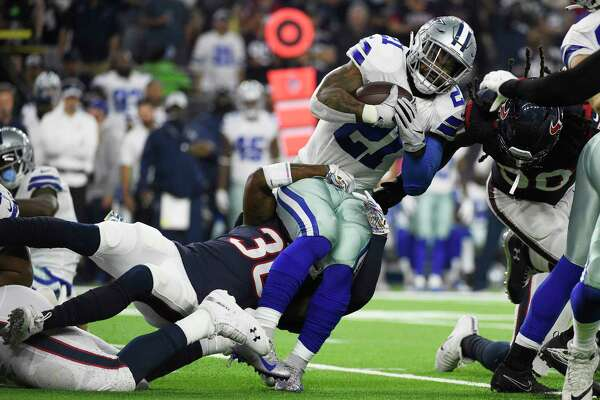 Dallas Cowboys running back Ezekiel Elliott (21) is stopped by Houston Texans defensive back Kayvon Webster (36) during the first half of an NFL football game, Sunday, Oct. 7, 2018, in Houston. (AP Photo/Eric Christian Smith)