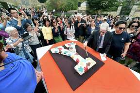 Yale University President Peter Salovey cuts a cake on Cross Campus in New Haven Tuesday during the fifth annual Founders Day, celebrating the founding of the university in 1701.