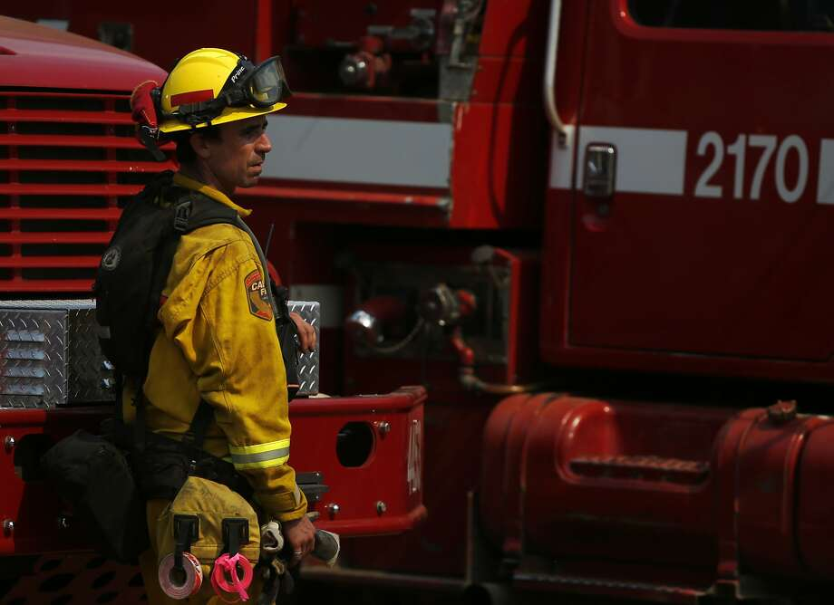 In this file photo a Cal Fire firefighter stands near a truck in a staging area for a Northern California wildfire firefight. Photo: Leah Millis / The Chronicle
