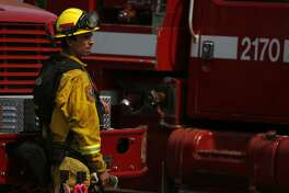 In this file photo a Cal Fire firefighter stands near a truck in a staging area for a Northern California wildfire firefight.