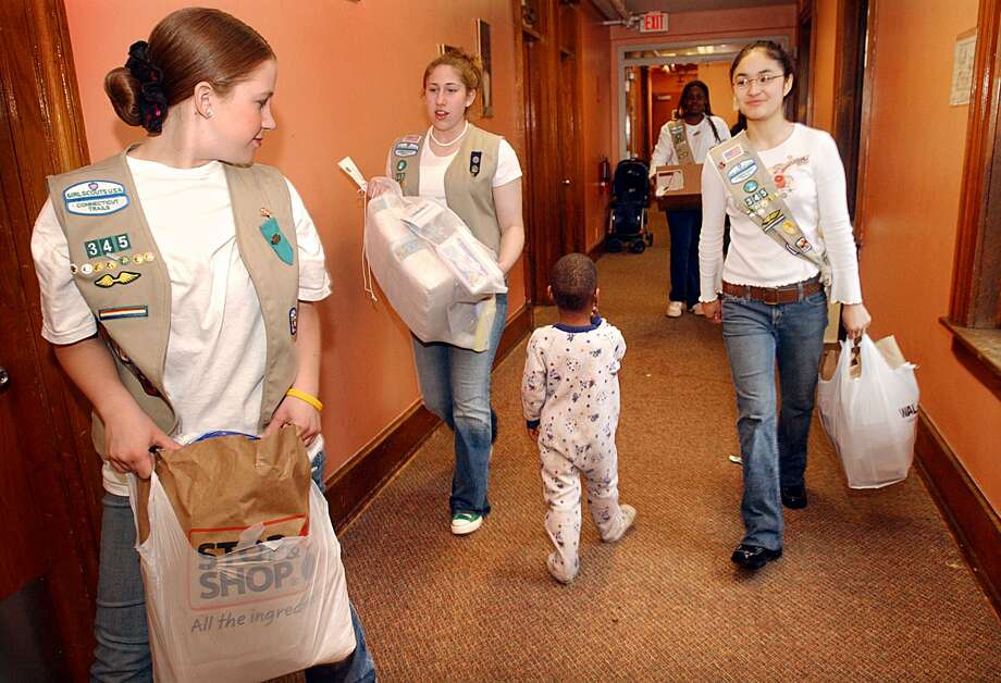 NEW HAVEN-GIRL SCOUT PROJECT-PHOTO/JEFF HOLT-JH00137E 4/23/05-Girl Scout Troop 345 Cadettes (L-R) Julie Rizzo, Alora Caraglio, Jenete Okeke and Julie Hoang carry bags of supplies they collected for donation to the attic at Life Haven. The scouts collected 73 kits to aid women and children transitioning from the shelter to places of their own for their Silver Award Service Project.(PHOTO/JEFF HOLT)