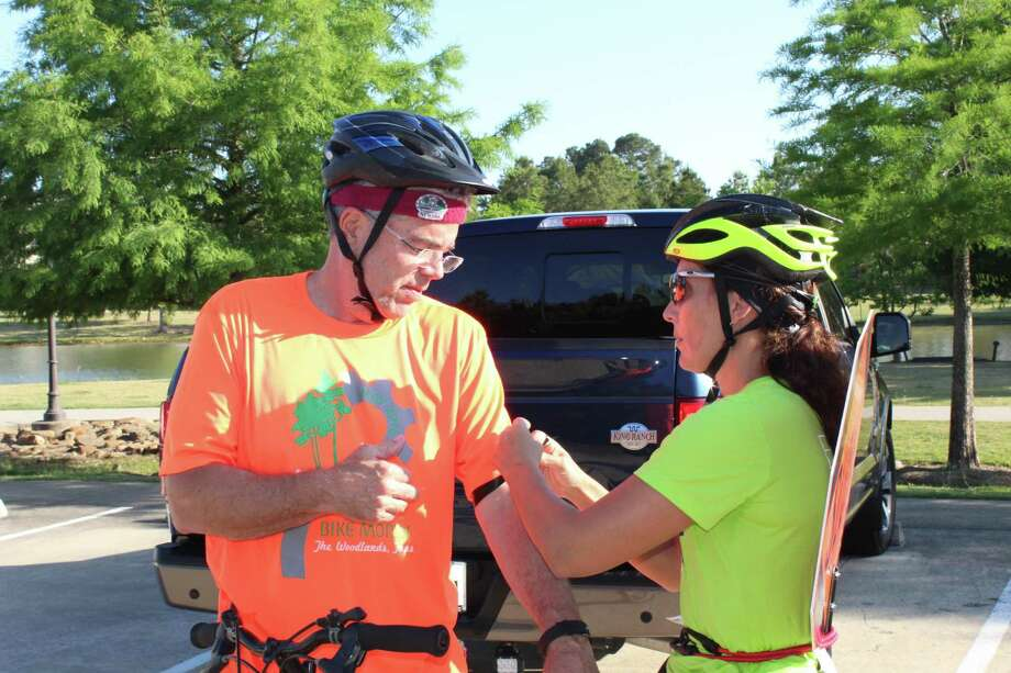 Fernanda Suarez, co-vice president of Bike The Woodlands Coalition, assists participants in the Ride of Silence on May 16 in tying black ribbons on their arms to honor cyclists who have been injured or killed by a motorist. Photo: Patricia Dillon / The Woodlands Villager