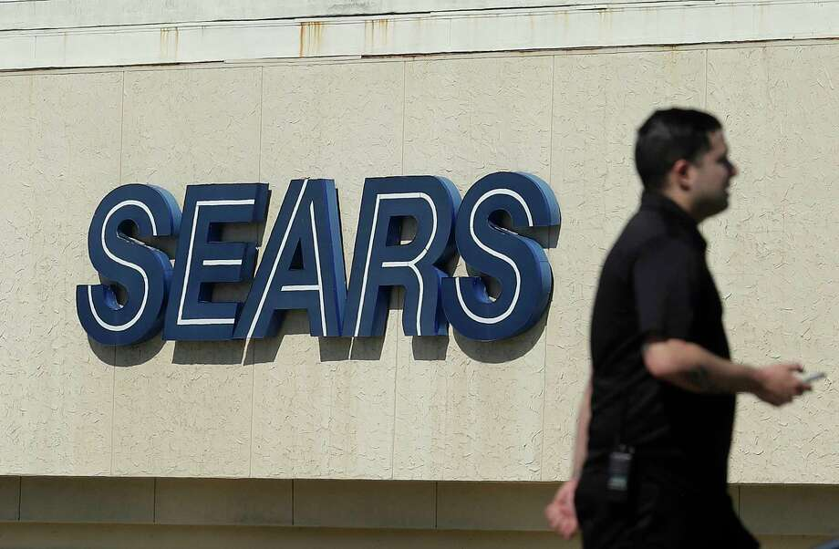 FILE- In this March 28, 2018, file photo, a man walks in front of a Sears sign in San Bruno, Calif. Sears is adding a restructuring expert to its board, suggesting that the company may be preparing to take drastic actions to survive or to protect its remaining assets. The Hoffman Estates, Ill., company, which also owns Kmart, said Tuesday, Oct. 9, it was bringing on board Alan Carr, managing member and CEO of Drivetrain LLC, a restructuring advisory firm. (AP Photo/Jeff Chiu, File) Photo: Jeff Chiu / Copyright 2018 The Associated Press. All rights reserved.