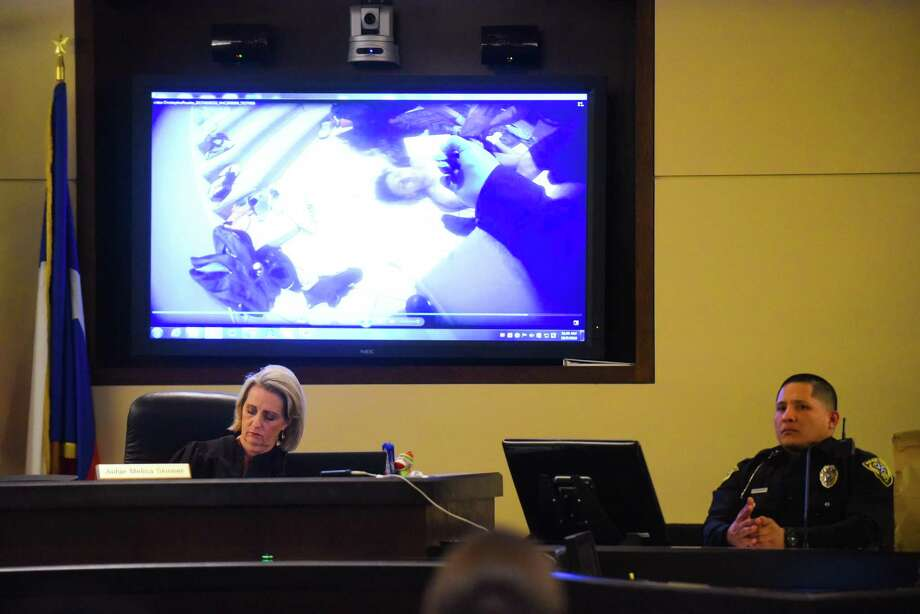 Judge Melisa Skinner, left, and Universal City Police Officer Christopher Rosales watch a bodycam video showing a wounded Jonathan Perales, who is accused of the capital murder death of Michael Clayton Robinson in Universal City. The scene was in 290th District Court on Tuesday, Oct. 9, 2018. Photo: Billy Calzada /Staff Photographer / San Antonio Express-News