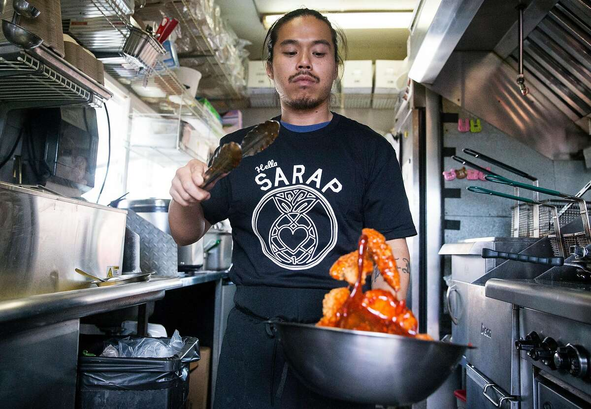 Cook Justin Encarnacion tosses chicken in a spicy sauce while inside Sarap Shop, a Filipino food truck, during a stop at SoMa Street Food Park in San Francisco, Calif. Tuesday, Oct. 9, 2018.