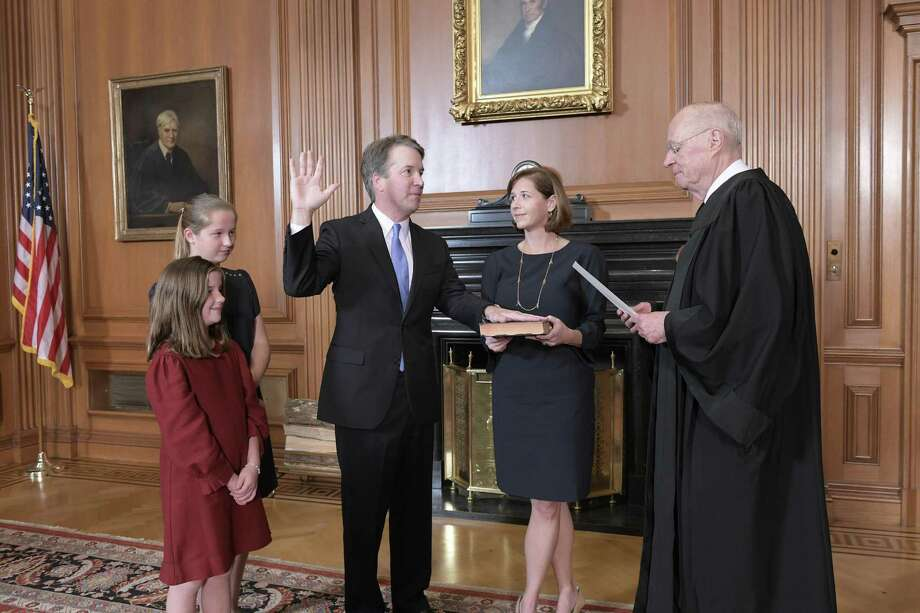 Retired Justice Anthony M. Kennedy, administers the Judicial Oath to Judge Brett M. Kavanaugh in the Justices' Conference Room at the Supreme Court Building on Saturday. Ashley Kavanaugh holds the Bible. Photo: Fred Schilling /TNS / Sipa USA
