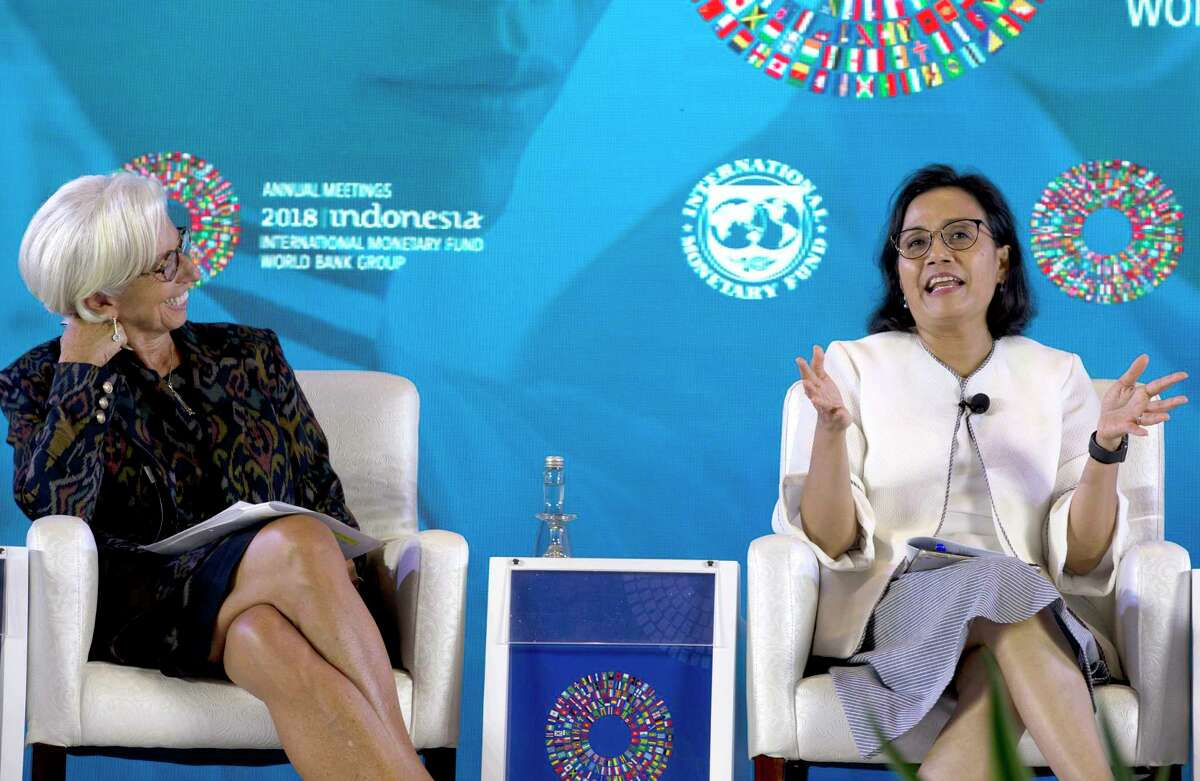 Managing Director of International Monetary Fund (IMF) Christine Lagarde, left, as she listens to Indonesia's Finance Minister Sri Mulyani during Empowering Women in the Workplace seminar at International Monetary Fund-World Bank meeting in Bali, Indonesia Tuesday, Oct. 9, 2018. (AP Photo/Firdia Lisnawati)