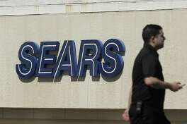 FILE- In this March 28, 2018, file photo, a man walks in front of a Sears sign in San Bruno, Calif. Sears is adding a restructuring expert to its board, suggesting that the company may be preparing to take drastic actions to survive or to protect its remaining assets. The Hoffman Estates, Ill., company, which also owns Kmart, said Tuesday, Oct. 9, it was bringing on board Alan Carr, managing member and CEO of Drivetrain LLC, a restructuring advisory firm. (AP Photo/Jeff Chiu, File)
