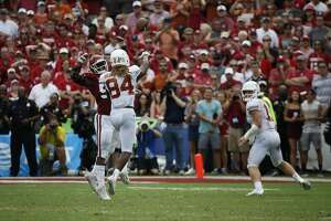 Oklahoma Sooners defensive end Kenneth Mann (55) pressures Texas Longhorns wide receiver Lil'Jordan Humphrey (84) as he passes to quarterback Sam Ehlinger (right) in the first half of an NCAA college football game, Saturday, Oct. 6, 2018, in Dallas, Texas. (AP Photo/Roger Steinman)