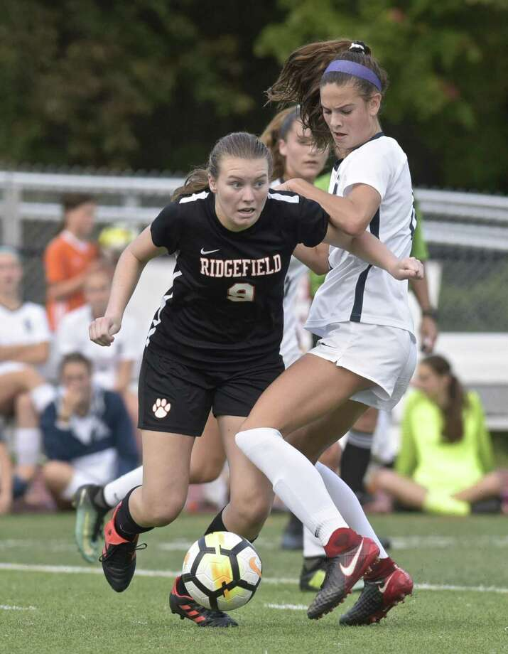 Ridgefield's Mackenzie Robson, left, tries to go around Staples' Mia Gonzalez in Tuesday's game at Ridgefield. Photo: H John Voorhees III / Hearst Connecticut Media / The News-Times