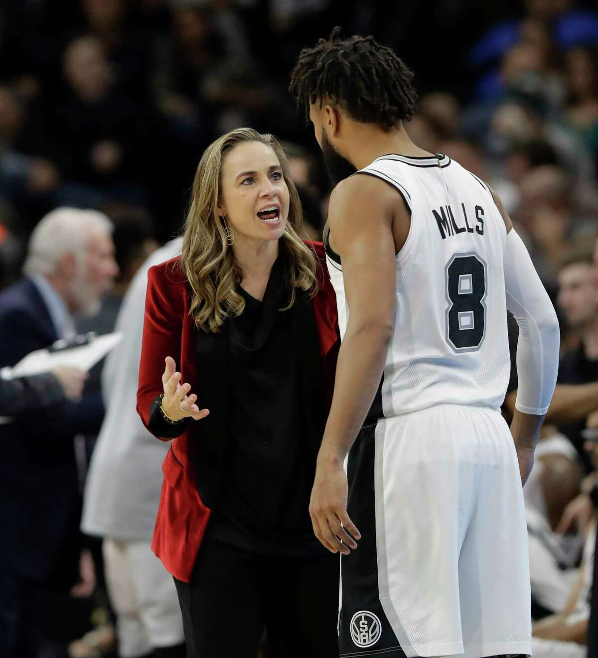 FILE - In this Dec. 26, 2017, file photo, San Antonio Spurs assistant coach Becky Hammon, left, talks with guard Patty Mills (8) during the second half of an NBA basketball game against the New York Nets, in San Antonio. This summer the NBA hired its first head coach born and raised outside North American, its first Hispanic-American head coach, and came perhaps as close as ever to having its first female head coach. Becky Hammon interviewed for the Milwaukee Bucks job, and it would be no surprise if the Spurs assistant soon gets another chance. (AP Photo/Eric Gay, File)