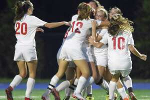 New Canaan's Olivia Bognon (13) celebrates with her teammates after scoring a goal against Darien in the second half of an FCIAC girls soccer game on Oct. 9, 2018 in Darien, Connecticut. New Canaan went on to win 1-0 against rival Darien.