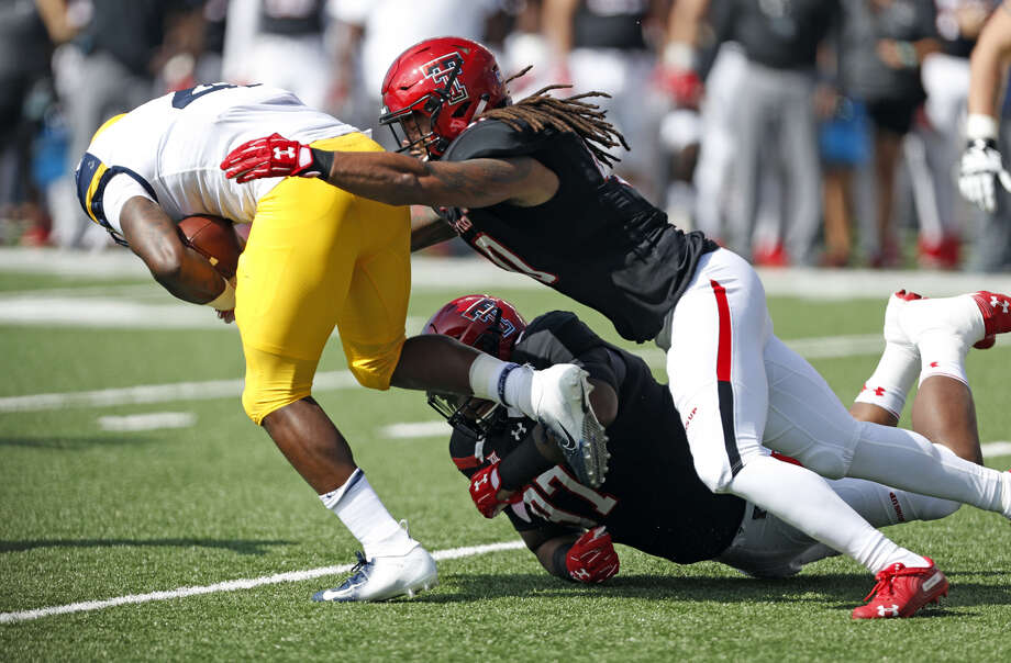 Texas Tech senior linebacker Dakota Allen (top) and sophomore defensive lineman Joseph Wallace combine on a tackle against West Virginia on Sept. 29 at Jones AT&T Stadium in Lubbock. After a week off, the Red Raiders play TCU on Thursday in Fort Worth. Photo: Brad Tollefson/Lubbock Avalanche-Journal