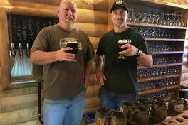 Owner Dave Littlefield and assistant brewer Tom Reardon with glasses of Sacred Grounds Coffee Porter at Housatonic River Brewing in New Milford on Thursday.