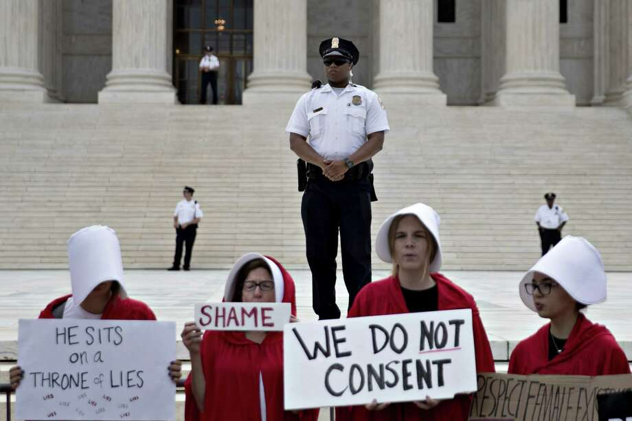 "U.S. Supreme Court police officers stand past demonstrators dressed in ""Handmaid's Tale"" costumes outside the court in Washington, D.C., U.S., on Tuesday, Oct. 9, 2018. Brett Kavanaugh will be at the end of the Supreme Court's bench when he hears his first argument as a justice today. He'll do so even as controversy continues to swirl over his selection by President Donald Trump and the sexual assault allegations that almost derailed it. Photographer: Andrew Harrer/Bloomberg Photo: Andrew Harrer / © 2018 Bloomberg Finance LP"