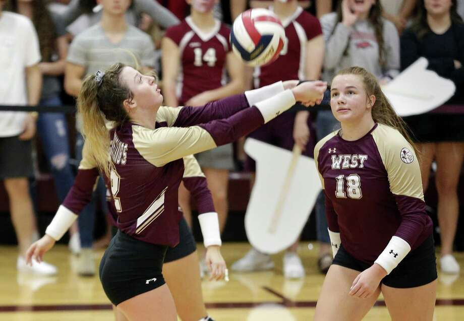 Magnolia West's Kara Wilson digs as Frankie Mullens (18) looks on during their match against Magnolia at Magnolia High School, Tuesday, Oct. 2, 2018 in Magnolia, TX. Photo: Michael Wyke, Houston Chronicle / Contributor / © 2018 Houston Chronicle