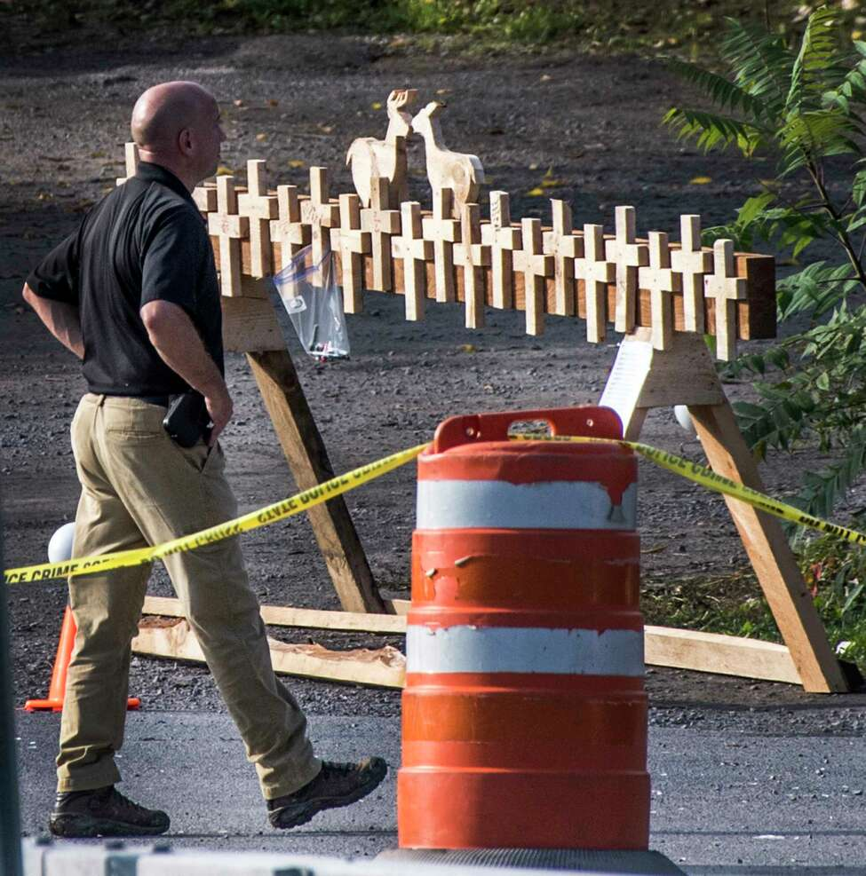Forensics Investigator from the New York State Police walks past a makeshift memorial at the site of the limousine accident Near the Apple Barrell tourist spot Tuesday Tuesday Oct.8, 2018 in Schoharie, N.Y. that took the lives of twenty people last weekend. (Skip Dickstein/Times Union)