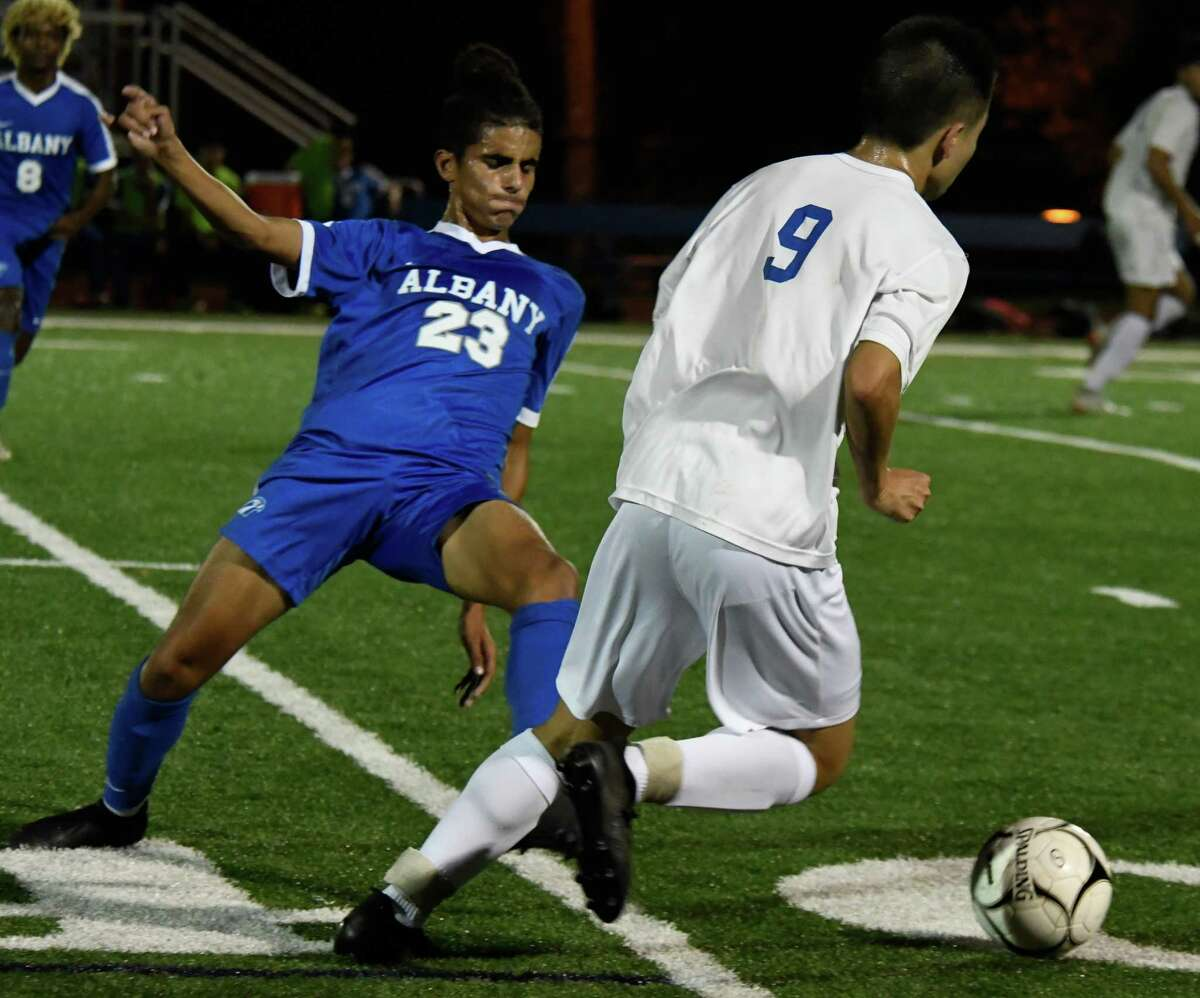Albany's Mohammad Yehia slides to kick the ball from Shaker's Ian Wu during a game on Tuesday, Oct. 9, 2018 in Albany, N.Y. (Jenn March, Special to the Times Union )