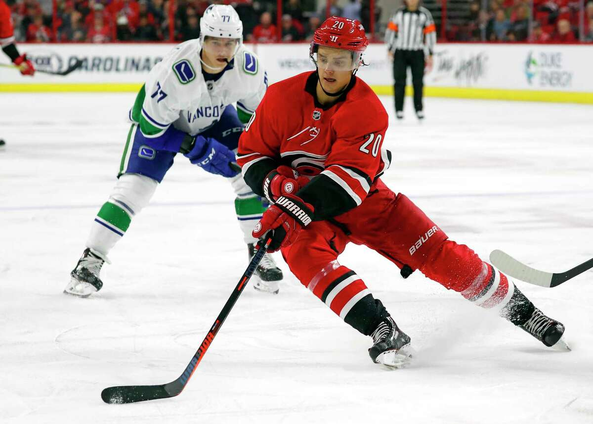 Carolina Hurricanes' Sebastian Aho (20) gathers in the puck in front of Vancouver Canucks' Nikolay Goldobin (77) during the second period of an NHL hockey game, Tuesday, Oct. 9, 2018, in Raleigh, N.C. (AP Photo/Karl B DeBlaker)