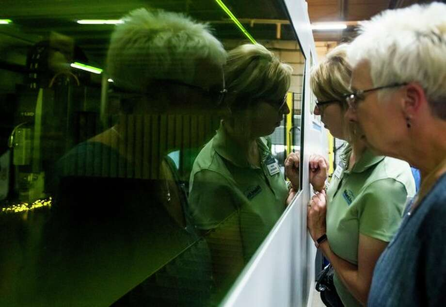 Tina Lewis, right, and Diane Chambers, second from right, both of the Midland Area Chamber of Commerce, peer through a window at the brand new Phoenix laser at Case Systems and BOSTONtec during a ribbon cutting event Tuesday at the facility in Midland. (Katy Kildee/kkildee@mdn.net)