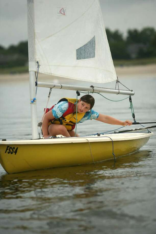 Marina Pipher, 13 of Fairfield, ducks under the boom during her sailing class with the Fairfield Sailing School off Jennings Beach in Fairfield recently. Photo: Brian A. Pounds / Connecticut Post