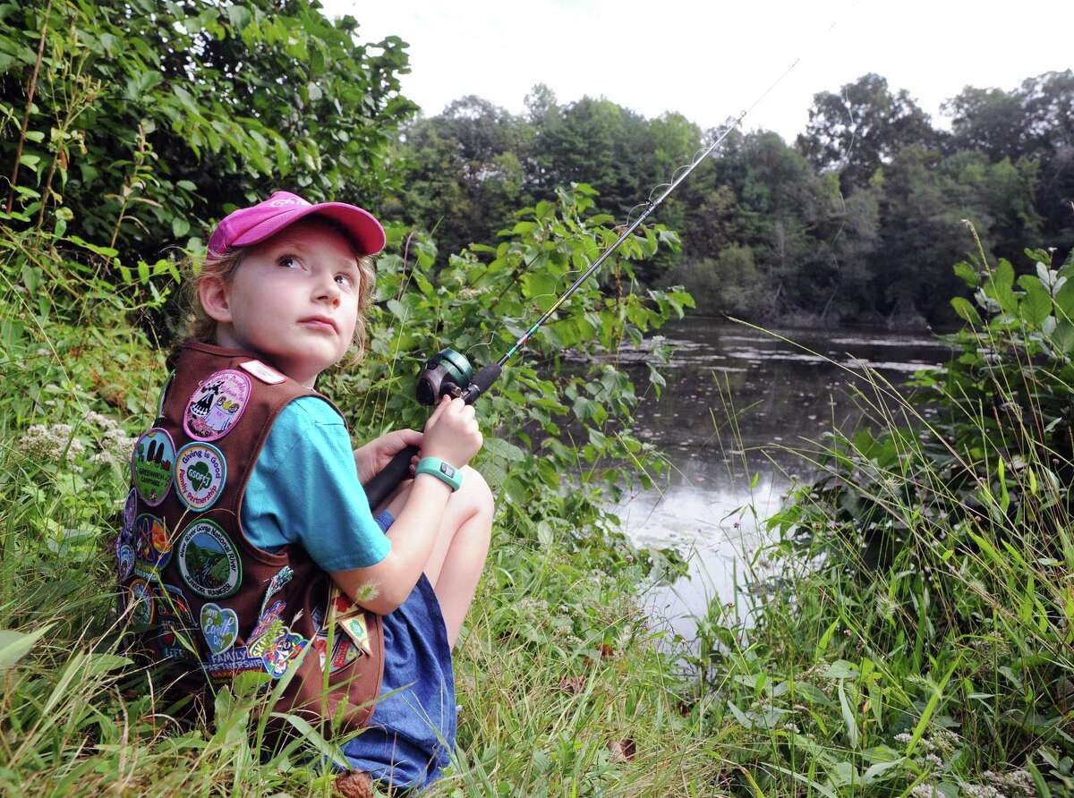 Briar Lissauer a Brownie in Cos Cob Troop 50301 sat in the grass as she fished in a lake during the Greenwich Girl Scouts
