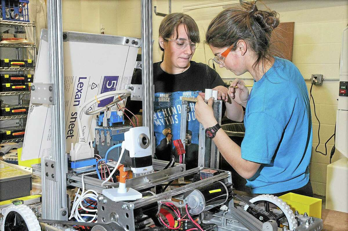 """A Mercy High School alumna, mechanical engineer and mentor with the robotics team, the TechTigers, positions the spacers on the """"dump"""" mechanism with a senior student on their robot, Raja."""