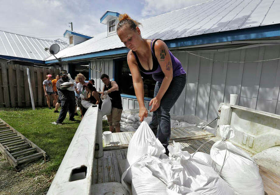 Krystal Day of Homosassa, Fla., leads a sandbag assembly line at the Old Port Cove restaurant Tuesday in Ozello, Fla. Employees were hoping to protect the restaurant as Hurricane Michael continues to churn in the Gulf of Mexico heading for the Florida panhandle. (AP Photo/Chris O'Meara)
