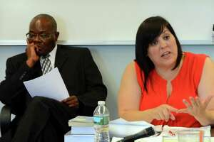 Bridgeport City Budget Chief Nestor Nkwo, left, looks on as Bridgeport School Board member Maria Pereira argues a proposed budget modification during a special meeting at Bridgeport City Hall building in Bridgeport, Conn., on Wednesday June 28, 2017. The board held the special meeting to decide if they will strike a deal with the city to allow the lighthouse summer program into city schools this summer.
