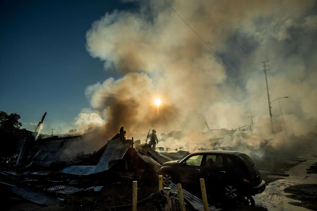 A firefighter stands amidst charred debris as he battles a smoky blaze at an industrial building in Oakland.