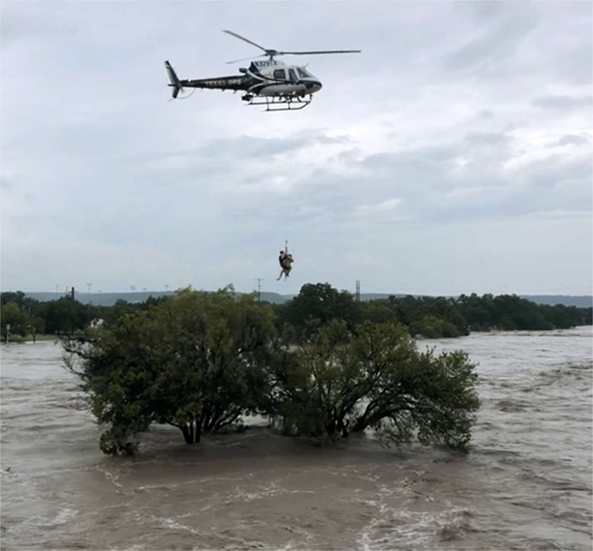 Texas DPS helicopter crew extracts a person who sought refuge in a tree as the South Llano and Llano rivers near Junction flooded early Monday. The flooding caused temporary closure of a handful of Hill Country state parks including popular South Llano River State Park.