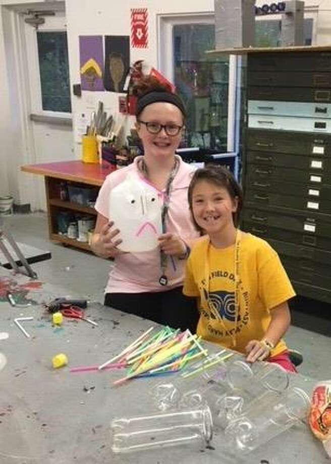 "Sixth-grade Country School students Michaela Troy and Rosie Liu construct a scarecrow for the Madison Chamber of Commerce's Scarecrows Invade Madison contest."" Photo: Louise Jackson / Contributed Photo"