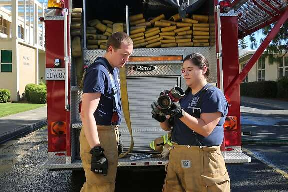 J.R. Rogers, fire chief of the Angwin Volunteer Fire Department, works with Selena Diaz, a volunteer firefighter for the past six years, in Angwin, Calif. on Tuesday, Sept. 11, 2018.