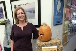 """Cromwell's Halloween scarecrow contest, running through the end of the month, gives residents and visitors to town hall a chance to survey a wide array of artistic creations and pick their favorites. Here, Amy Saada, the senior center and human services director, shows off the inventive ballot """"box."""""""