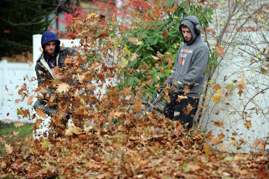 A crew from Stamford based Caretaker Landscaping blow leaves into a pile on Merriman Road for the city to pick up in Stamford, Conn. on Monday, Nov. 20, 2017. Photo: Michael Cummo / Hearst Connecticut Media / Stamford Advocate