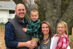 Stacy (Delaney) Rohr poses with her family, husband Chris, son Lincoln, and daughter Lynlee outside the family's home in Columbia, Mo.
