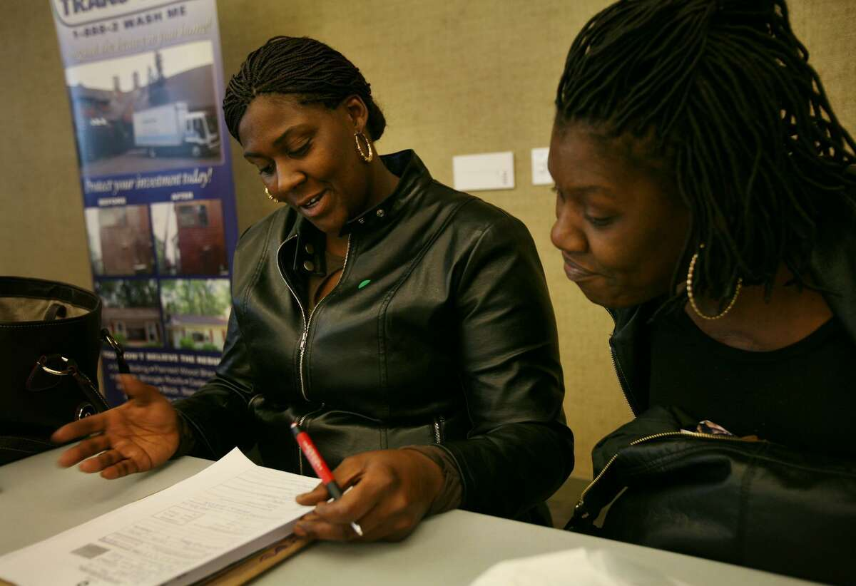 Brian A. Pounds/ Staff Photographer Friends L'Toya Bell, left of Norwalk, and Simone VanBrakle of Bridgeport, fill out job applications at the community job fair at Housatonic Community College in Bridgeport on Wednesday. The pair said that between the two they had filled out 27 applications over the course of the morning.