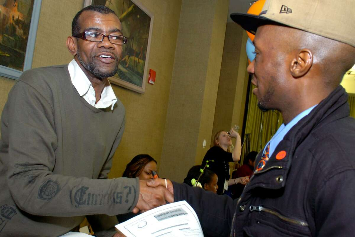 Victor Newton from the Newton-Foster Home Care Agency in Bridgeport greets Eamon Lloyd of Bridgeport at a job fair at Housatonic Community College in Bridgeport, Conn. Wednesday, March 16th. 2011.